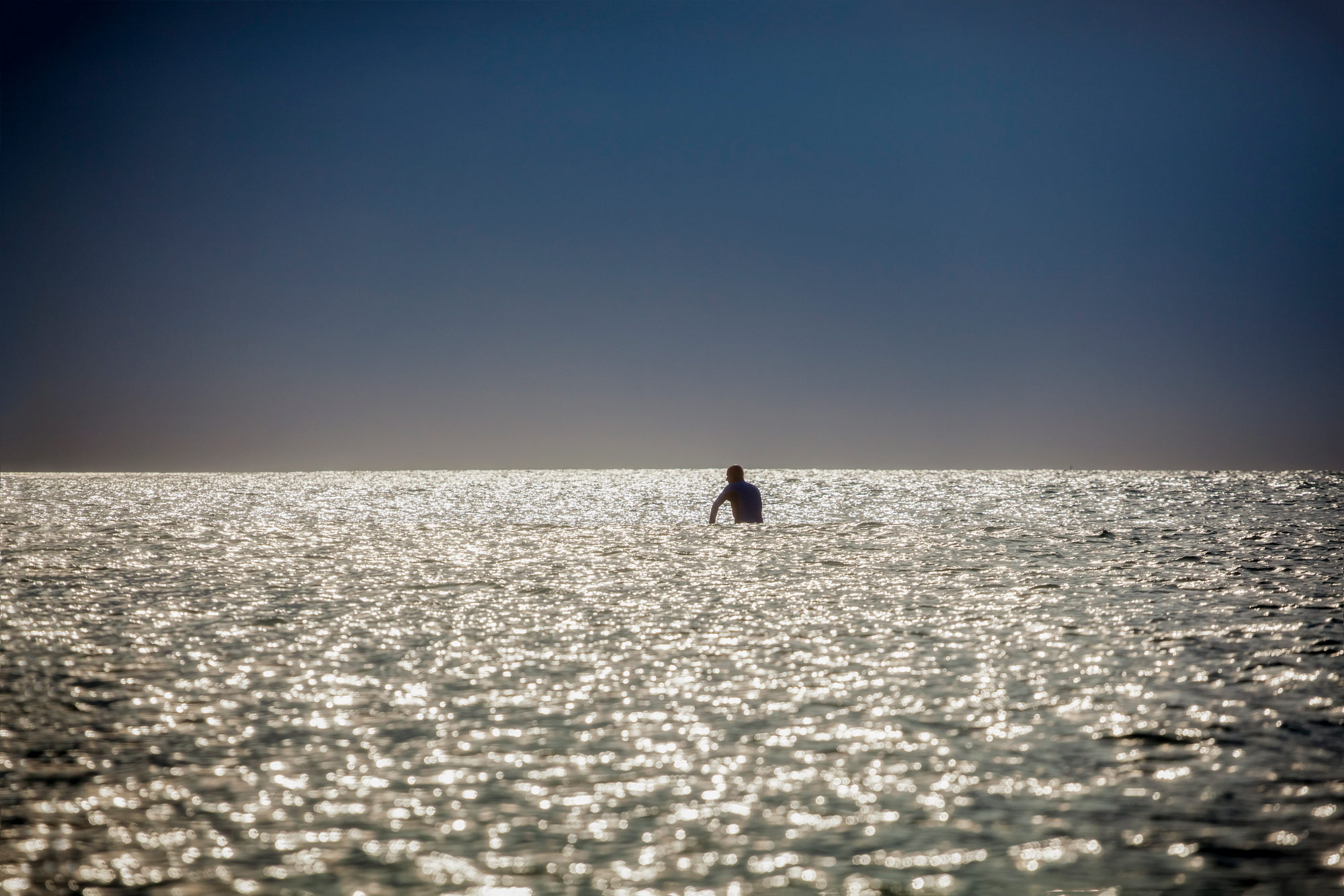 Texas surfer sits alone on his board in the water