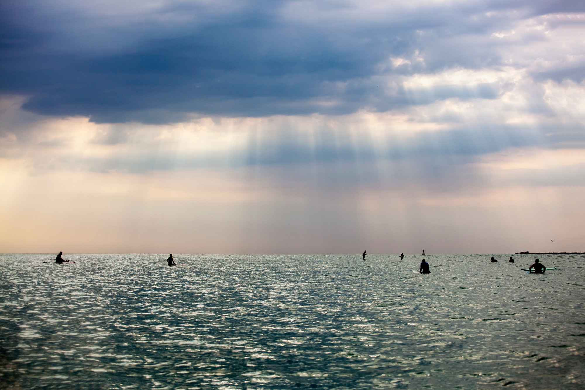 Texas surfers in lineup with dramatic sky