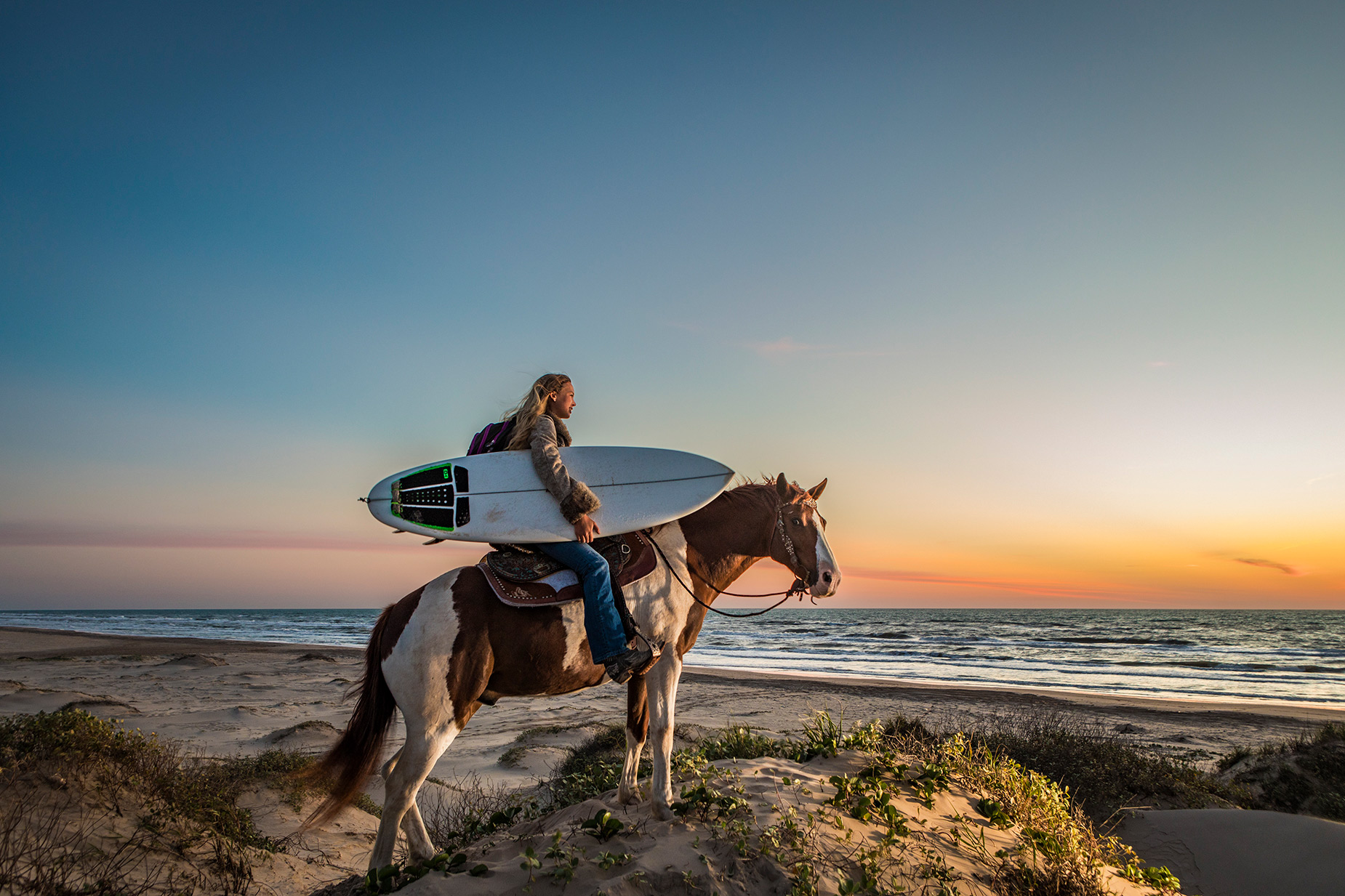 Texas surfer on her horse in the dunes at sunrise