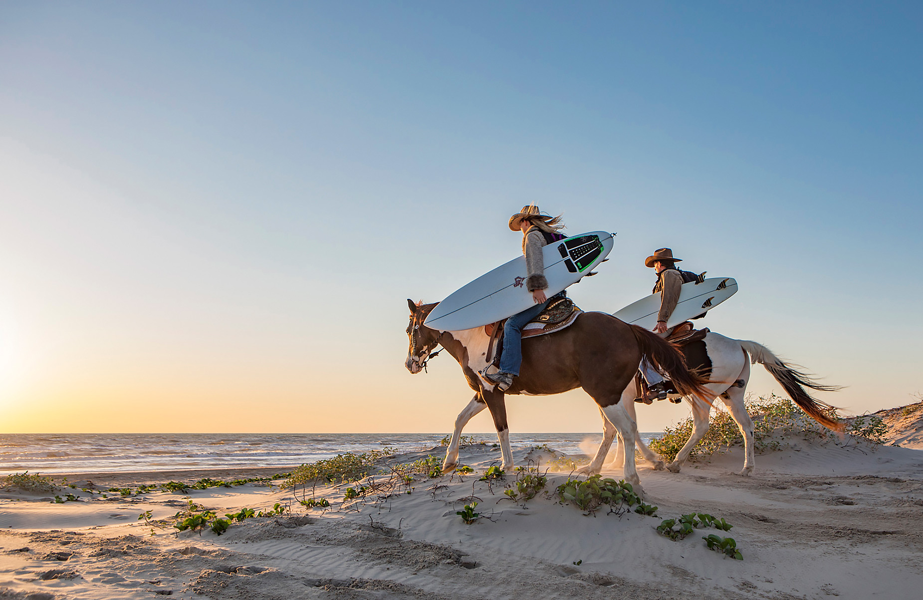 Texas surfers on horseback in the dunes at sunrise