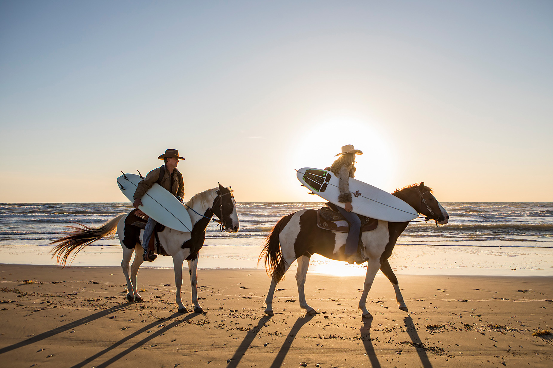 Texas surfers on horseback on the beach at sunrise
