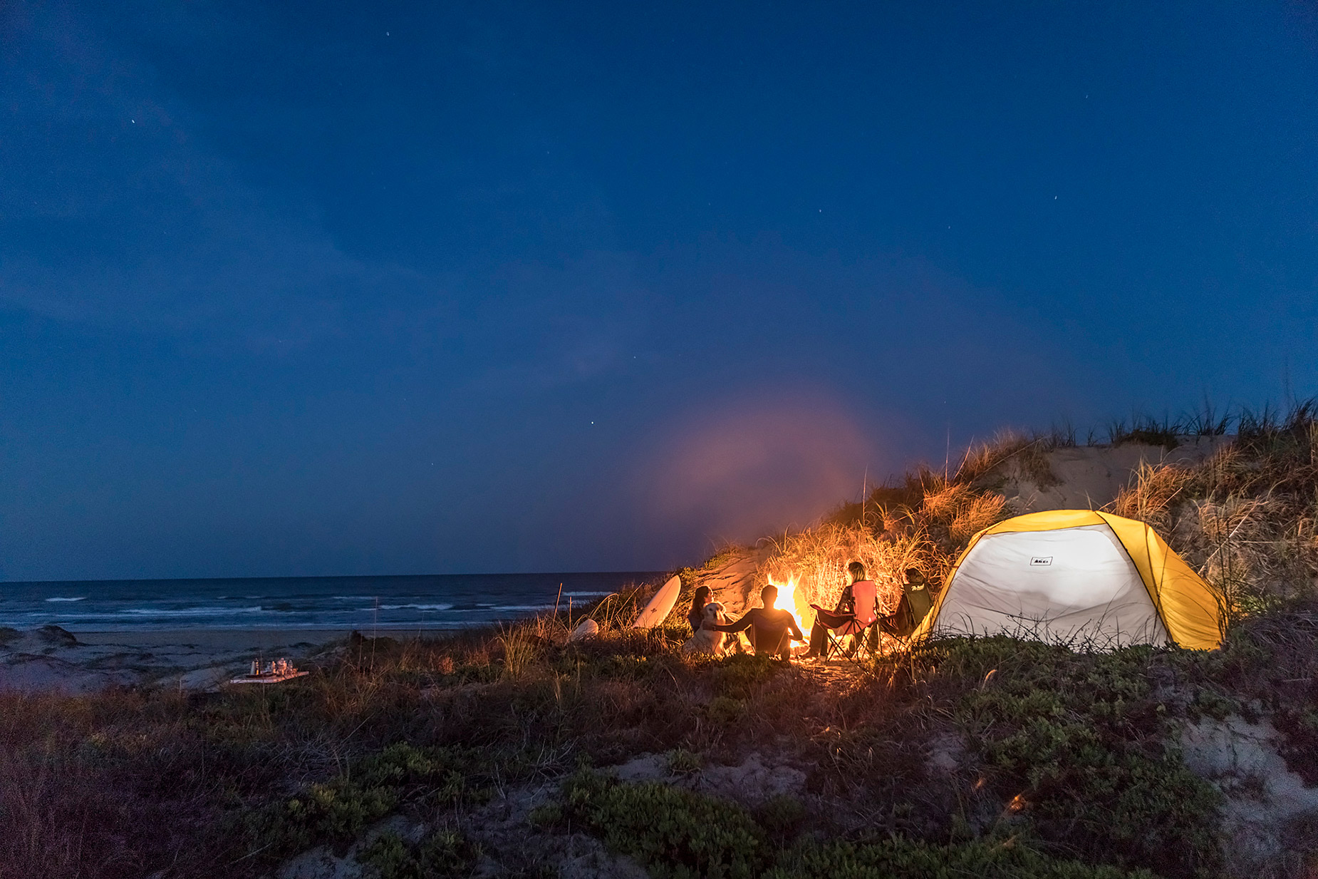 Family camping on Texas beach in dunes at dusk