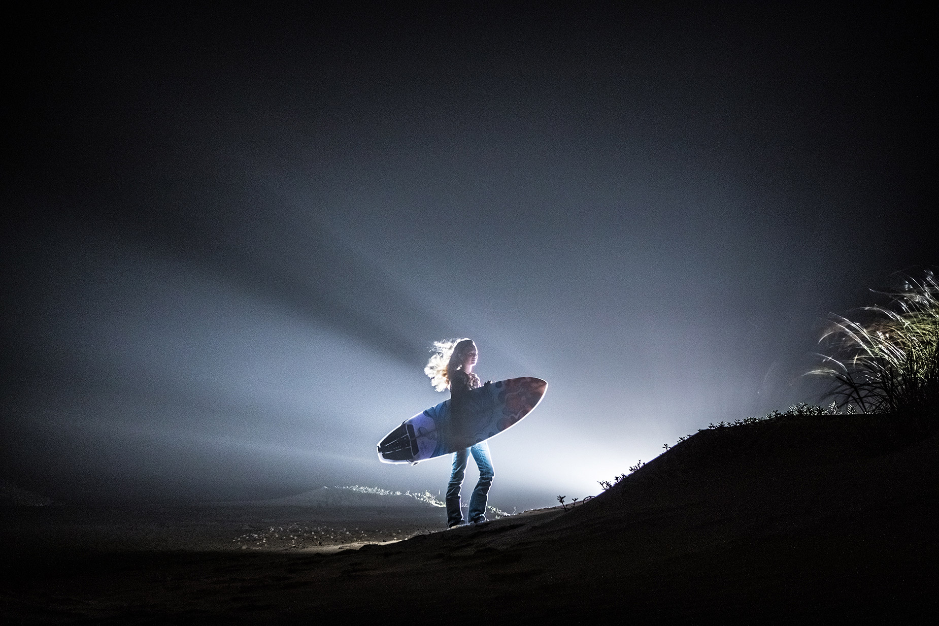 Girl holding surf board at night in dramatic backlight