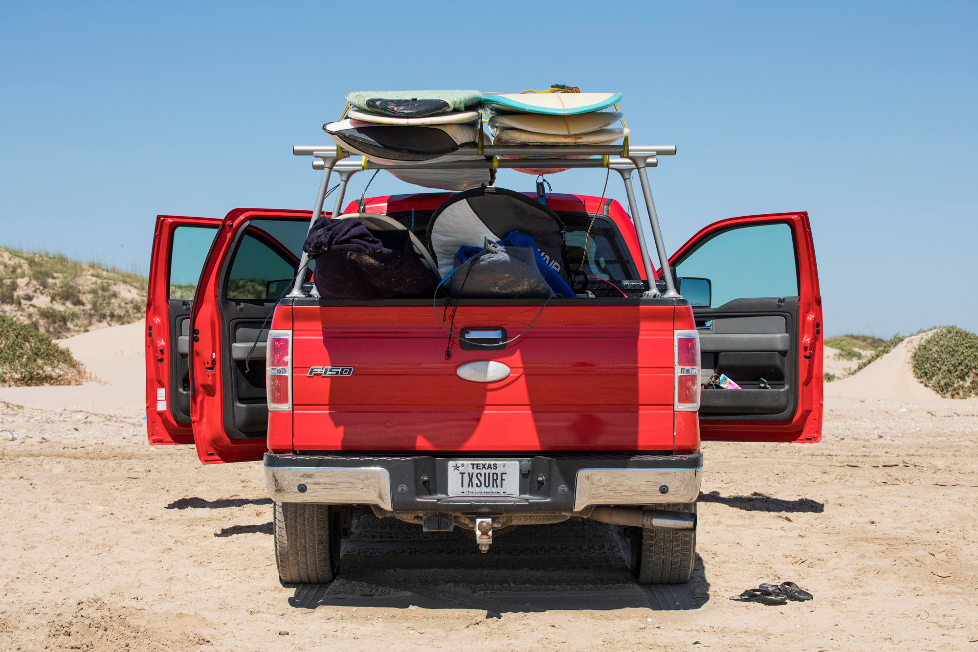 Red Texas Ford truck with surfboards