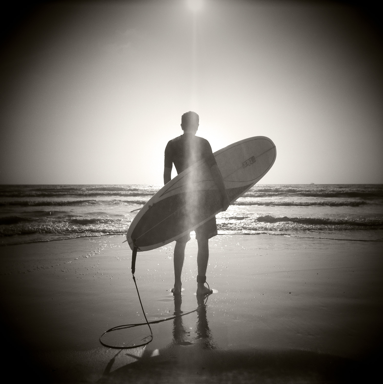 Lone Surfer holding surfboard
